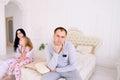 Couple quarrel and child upset, sitting bed in white interior
