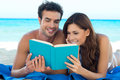 Couple Reading Book At The Beach Royalty Free Stock Photography
