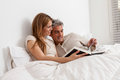 Couple reading a book lying in the bed and Stock Images