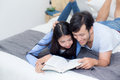 Couple reading a book together in bedroom on the morning. Royalty Free Stock Photo