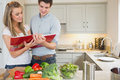Couple reading cookbook together in a kitchen Stock Photography