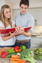 Couple reading cookbook together in kitchen Royalty Free Stock Photos