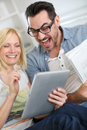 Couple reading funny news on tablet both internet and paper Royalty Free Stock Images