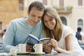 Couple reading guidebook at cafe smiling young outdoor looking of rome Stock Photos