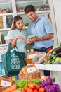Couple reading product details in supermarket mid adult while shopping vegetables Royalty Free Stock Photos