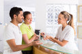 Couple with receptionist at clinic young smiling married talking smiling secretary reception in the Stock Photography