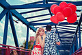 Couple with red balloons young happy on the bridge Royalty Free Stock Photography