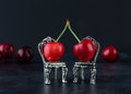 Couple of red cherries on two silver chairs with blurred cherrie Royalty Free Stock Photo