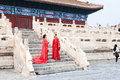 Couple in red dresses on steps of Hall for Worship Royalty Free Stock Photo