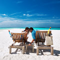 Couple relax on a beach at Maldives Stock Images