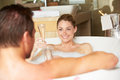 Couple relaxing in bath drinking champagne together bubble smiling to each other Stock Image