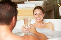 Couple relaxing in bath drinking champagne together bubble smiling to each other Royalty Free Stock Photo