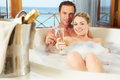 Couple relaxing in bath drinking champagne together bubble smiling to each other smiling to camera Royalty Free Stock Images