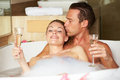 Couple relaxing in bath drinking champagne together smiling Stock Photography