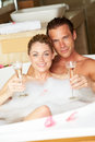 Couple relaxing in bath drinking champagne together smiling to camera Stock Photography