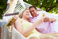 Couple relaxing in beach hammock drinking champagne smiling to each other Royalty Free Stock Images