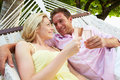 Couple relaxing in beach hammock drinking champagne smiling to each other Royalty Free Stock Photography
