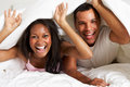 Couple relaxing in bed hiding under duvet smiling to camera Stock Images