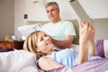 Couple relaxing in bed with newspaper and digital tablet at home breakfast background Royalty Free Stock Image