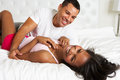 Couple relaxing in bed wearing pajamas smiling to each other Stock Photos