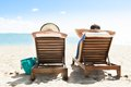 Couple relaxing on deck chairs at beach resort Royalty Free Stock Photo