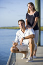 Couple relaxing with drink on dock by water Royalty Free Stock Photography