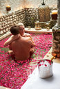 Couple relaxing in flower petal covered pool at spa smiling to camera Royalty Free Stock Photo