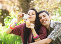 Couple relaxing in the park with bubble blower spring time Stock Photo