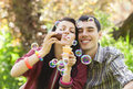 Couple relaxing in the park with bubble blower spring time Stock Photos