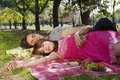 Couple relaxing on picnic blanket portrait of beautiful young women with men in park Stock Photography