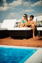 Couple relaxing sexy young near pool on a beach bed Stock Photos