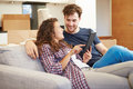 Couple relaxing on sofa with digital tablet in new home looking at each other smiling Stock Photography