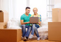 Couple relaxing on sofa with laptop in new home moving technology and concept smiling Stock Photo