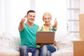 Couple relaxing on sofa with laptop in new home moving technology and concept smiling and showing thumbs up Royalty Free Stock Images