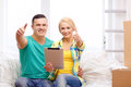 Couple relaxing on sofa with tablet pc in new home moving technology and concept smiling computer showing thumbs up Stock Photography