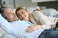 Couple relaxing on sofa together mature in peaceful scene Stock Photography
