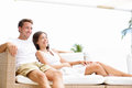 Couple relaxing together in sofa romantic young happy multi ethnic lying at home resting having fun maybe Stock Photos
