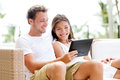 Couple relaxing together in sofa with tablet pc computer having fun romantic young happy multiracial love sitting at Stock Photography