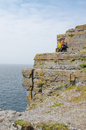 Couple resting in dun aengus an ancient fort cliffs aran islands republic of ireland Royalty Free Stock Images