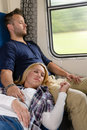 Couple resting with eyes closed in train Stock Images