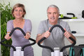 Couple riding exercise bikes Royalty Free Stock Image