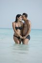 Couple romancing in water on the beach daytime Royalty Free Stock Image