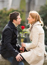 Couple with a rose kissing on valentines day young men giving his girlfriend and celebrating Royalty Free Stock Image