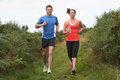 Couple on run in countryside running towards camera Royalty Free Stock Image