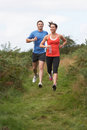Couple on run in countryside running towards camera Stock Photo