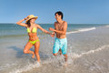 Couple running on beach wide shot of latin young man and woman through surf florida Royalty Free Stock Images