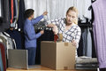 Couple running online clothing store packing goods for dispatch young Stock Images
