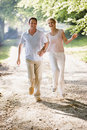 Couple running outdoors holding hands and smiling Royalty Free Stock Photography