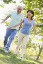 Couple running outdoors in park smiling Royalty Free Stock Images