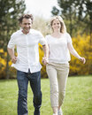 Couple running through park holding hands Royalty Free Stock Image